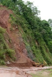 A backhoe moves dirt and mud from a mudslide along a highway